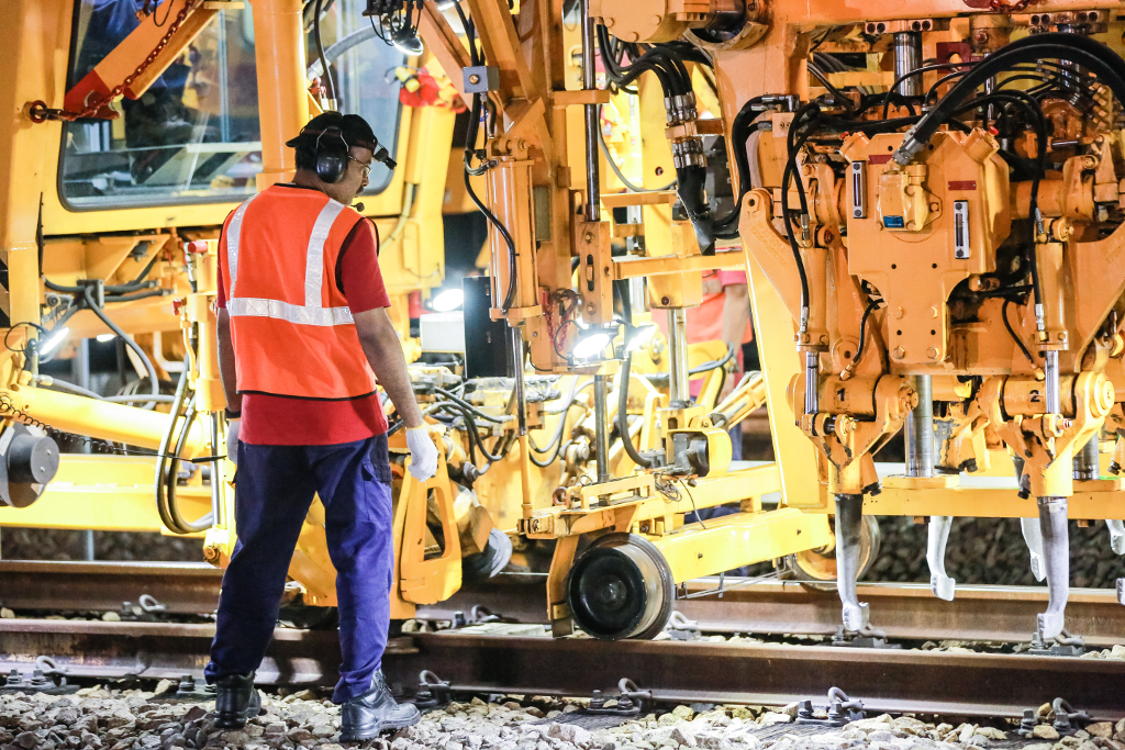 The Track Tamping Vehicle uses vibrations to settle the ballast, which are the small rocks found at the tracks.