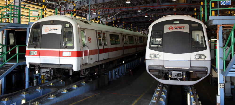 A Siemens C651 train (left) flanked by a Kawasaki Heavy Industries & CSR Qingdao Sifang C151A train in a train maintenance bay. The Siemens C651 trains are the only NSEWL train type painted in a white paint scheme with a red stripe.
